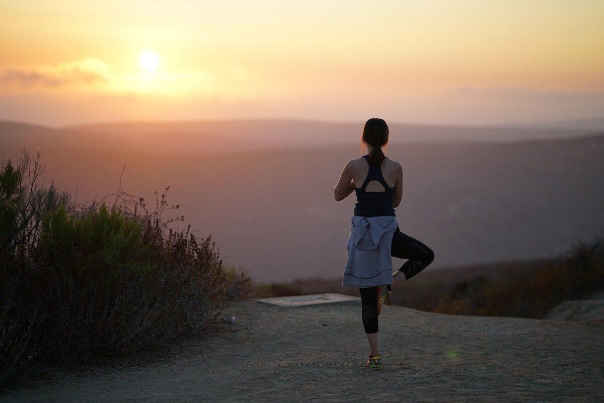 Löpare som gör yogaövning på en strand vid en soluppgång.